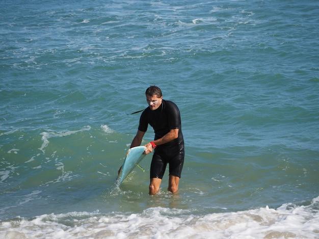 Lebensstil. ein müder surfer kommt aus dem wasser. mit dem surfbrett. Premium Fotos