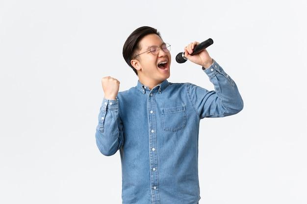 Lebensstil, freizeit und menschenkonzept. sorgloser glücklicher asiatischer mann, der genießt, beim karaoke zu singen, mikrofon und faustpumpe im entzücken hält und über weißer wand auftritt Kostenlose Fotos