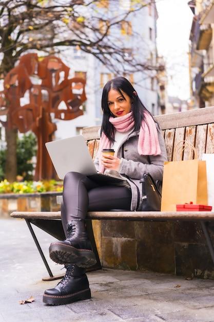 Lebensstil, kaukasisches brünettes mädchen, das mit laptop in einem park arbeitet, sitzt auf einer bank Premium Fotos