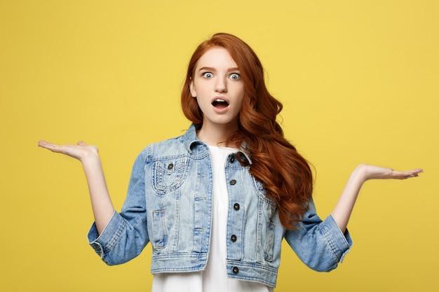 Lebensstil-konzept: überraschte junge frau mit der hand auf seite über goldenem gelbem hintergrund Premium Fotos