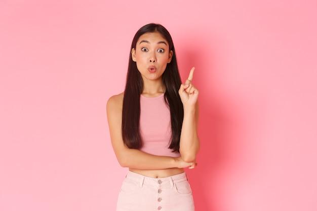 Lebensstil, schönheit und frauenkonzept. kreative attraktive asiatische mädchen in sommerkleidung haben lösung, zeigefinger heben und ihre idee sagen, überlegen sie sich großen plan, stehende rosa wand Kostenlose Fotos