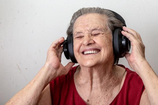 Lebensstil und leutekonzept: lustige hörende musik alter dame und tanzen auf weißem hintergrund. tragende gläser der älteren frau, die zur musik hört auf seinen kopfhörern tanzen. Premium Fotos