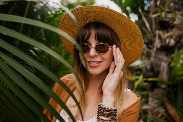 Lebensstilporträt der brünetten frau im strohhut, der auf tropischen palmblättern aufwirft Kostenlose Fotos