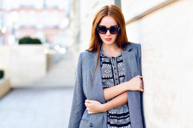 Lebensstilporträt der frau, tragendes elegantes glamourjackenkleid und vintage-sonnenbrille, getönte warme farben, positive stimmung. Kostenlose Fotos