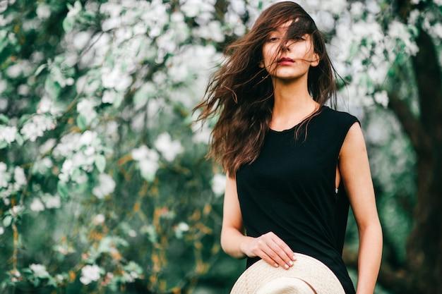 Lebensstilporträt des brunettemädchens im schwarzen kleid mit strohhut in ihren händen über dem blühenden apfelbaum auf hintergrund. Premium Fotos