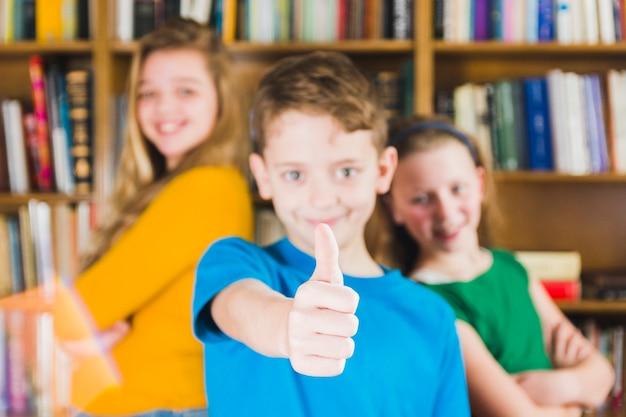 Lebhafte kinder, die in der bibliothek stehen Kostenlose Fotos