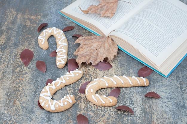 Lebkuchen und offenes buch mit blättern auf marmoroberfläche. hochwertiges foto Kostenlose Fotos