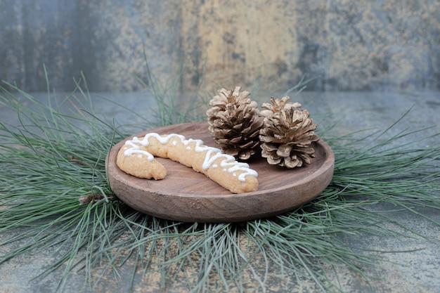 Lebkuchen und tannenzapfen auf holzteller. hochwertiges foto Kostenlose Fotos