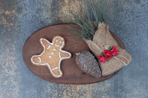 Lebkuchenmann-keks, tannenzapfen und gräser in sackleinen auf holzteller. hochwertiges foto Kostenlose Fotos