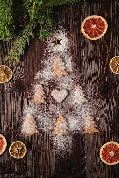 Lebkuchenplätzchen in der weihnachtstannenbaumform und mit puderzucker auf holztisch, zitrusfruchttrockenfrüchte, tannenbaumast, draufsicht Premium Fotos