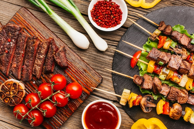 Lecker gegrilltes fleisch und steak mit frischem gemüse Kostenlose Fotos