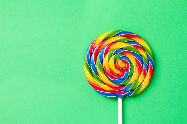 Leckere appetitliche party zubehör sweet swirl süßigkeiten lollypop auf grünem hintergrund draufsicht Kostenlose Fotos