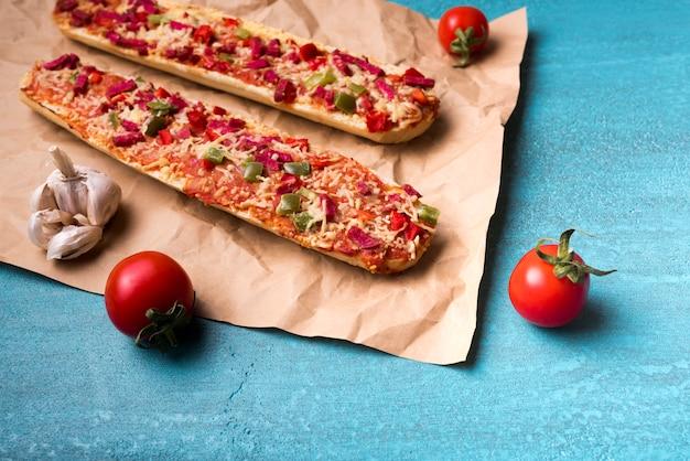 Leckere baguette-pizza; kirschtomate und -knoblauch auf braunem papier über blauem konkretem hintergrund Kostenlose Fotos