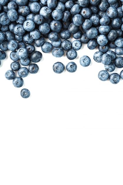 Leckere blaubeerfrüchte sind auf einem weißen hintergrund verstreut Premium Fotos