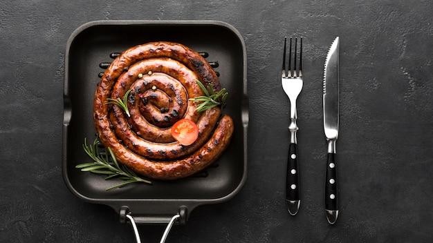 Leckere bratwurst in einer pfanne mit besteck Premium Fotos
