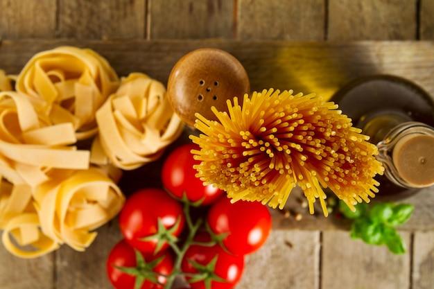 Leckere bunte frische italienische lebensmittel-konzept mit verschiedenen pasta spaghetti, frischen basilikum, tomaten, gewürze. kochen konzept. platz für text. nahansicht. Kostenlose Fotos