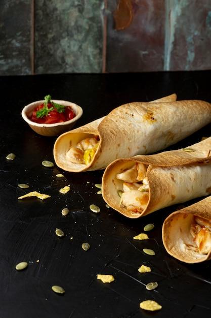 Leckere burritos mit hähnchen und sauce in schüssel Kostenlose Fotos