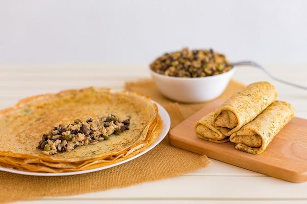 Leckere dünne pfannkuchen mit füllungen. gefüllte crepes mit hackfleischpilzen und marinierter gurke. Premium Fotos
