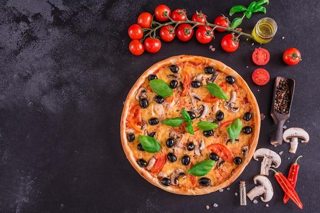 Leckere frische heiße pizza vor einem dunklen hintergrund Premium Fotos