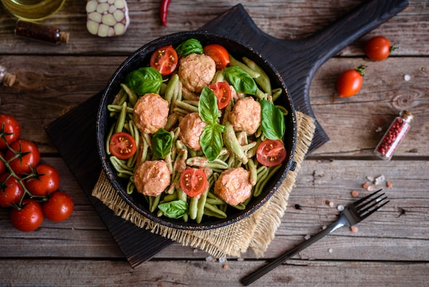 Leckere frische pasta mit fleischbällchen, sauce, kirschtomaten und basilikum Premium Fotos
