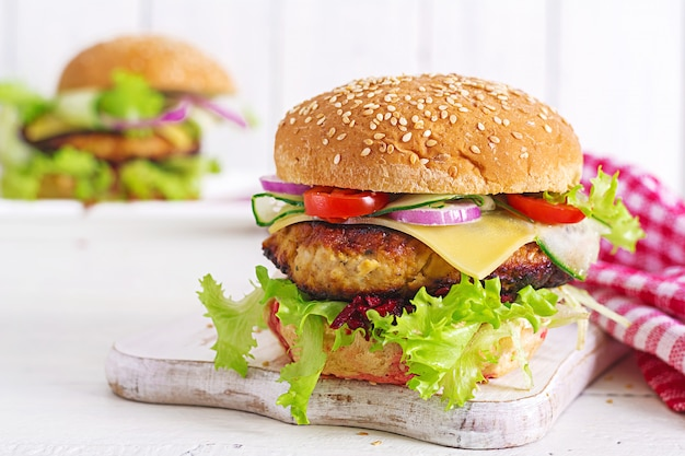 Leckere gegrillte hausgemachte hamburger mit burger huhn, tomaten, käse, gurken, salat und rote beete. Premium Fotos