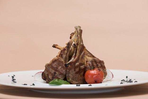 Leckere gegrillte lammrippen, mit grilltomate und dekoriert mit rettich, spinat, grünem blatt Premium Fotos