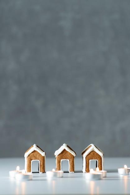 Leckere glasierte gemalte lebkuchenhäuser und kerzen auf grauem hintergrund. vertikaler rahmen. speicherplatz kopieren Premium Fotos