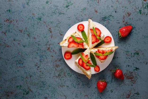 Leckere hausgemachte erdbeerkuchenscheiben mit sahne und frischen erdbeeren, draufsicht Kostenlose Fotos