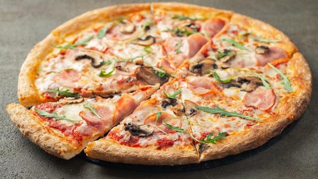 Leckere heiße pizza mit schinken und champignons. Premium Fotos