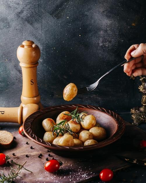 Leckere kartoffeln ganz gekocht gesalzen und gewürzt um frische rote tomaten auf der dunklen oberfläche Kostenlose Fotos