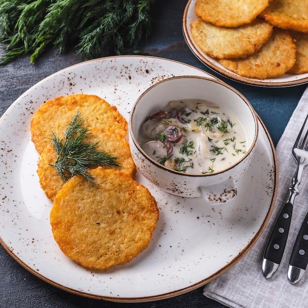 Leckere kartoffelpuffer mit würstchen in soße. machanka. traditionelles belarussisches gericht. Premium Fotos