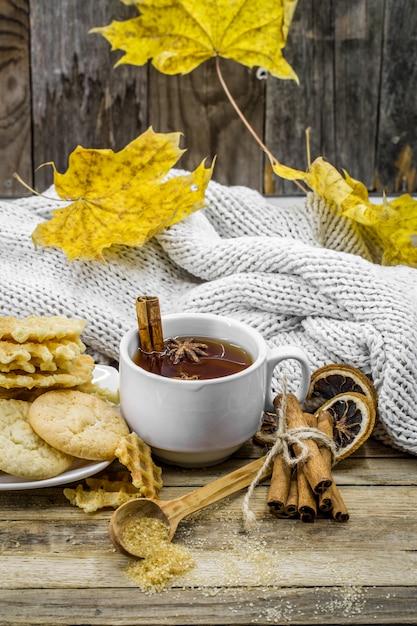 Leckere kekse und eine tasse heißen tee mit einer zimtstange und einem löffel braunem zucker auf holz mit gelbem herbstlaub, Kostenlose Fotos