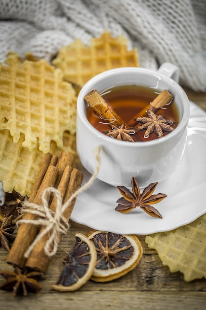 Leckere kekse und eine tasse heißen tee mit einer zimtstange und einem löffel braunem zucker auf holz Kostenlose Fotos