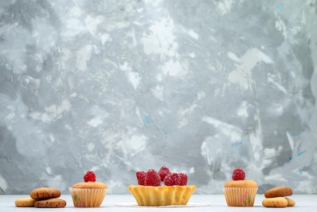 Leckere kleine kuchen mit himbeeren zusammen mit keksen auf leichten, kuchen keks süße beere Kostenlose Fotos