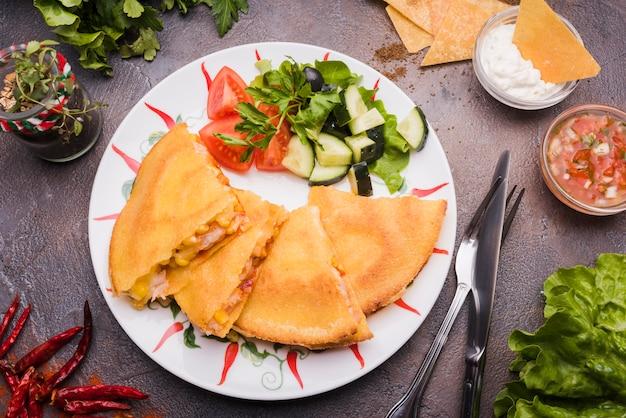 Leckere kuchen in der nähe von gemüsesalat auf teller unter nachos mit sauce und besteck Kostenlose Fotos