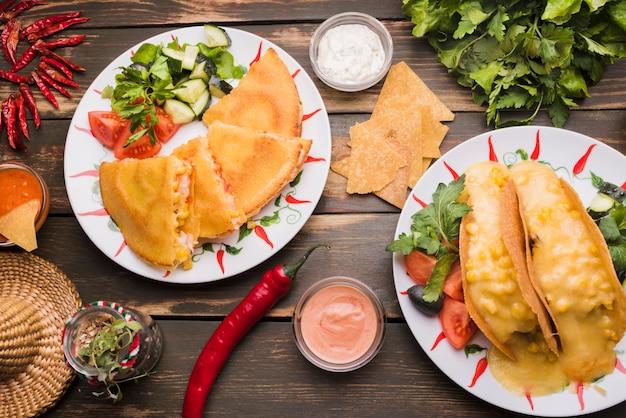 Leckere kuchen in der nähe von gemüsesalaten auf tellern zwischen saucen und chili Kostenlose Fotos