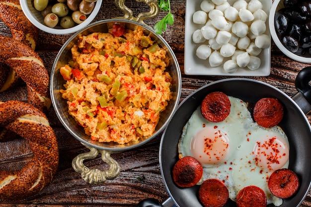 Leckere mahlzeiten in einem topf und einer pfanne mit türkischem bagel, essiggurken-draufsicht auf einer holzoberfläche Kostenlose Fotos