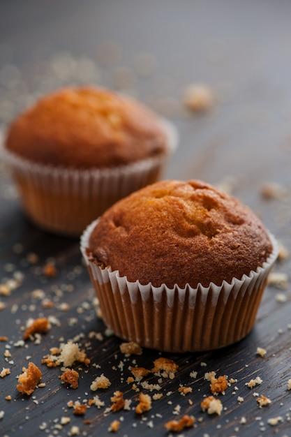 Leckere muffins mit den krümeln auf der holzoberfläche Kostenlose Fotos
