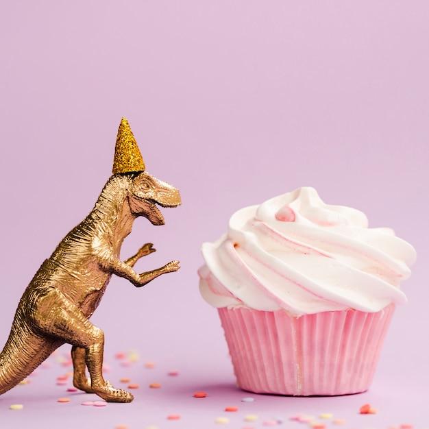 Leckere muffins und dinosaurier mit geburtstag hut Kostenlose Fotos