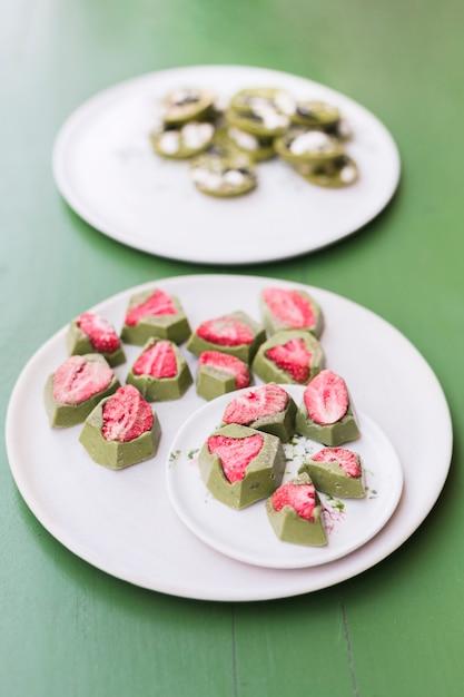 Leckere nachtische mit erdbeere auf weißen keramischen platten über grüner tabelle Kostenlose Fotos