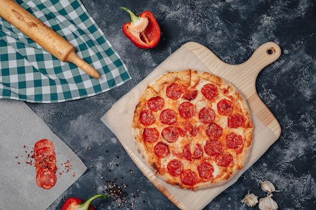 Leckere neapolitanische pizza auf einer tafel mit verschiedenen zutaten, freier platz für text Kostenlose Fotos