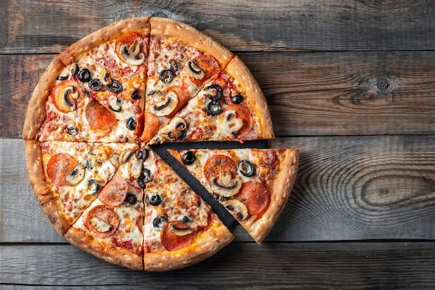 Leckere pepperonipizza mit pilzen und oliven. Premium Fotos