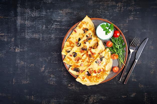 Leckere pfannkuchen mit pilzen, schinken und käse, rucola, tomaten und sauerrahm Premium Fotos