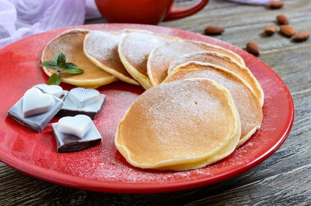 Leckere pfannkuchen mit puderzucker auf einem roten teller auf einem holztisch. festliches dessert zum thema liebe. Premium Fotos