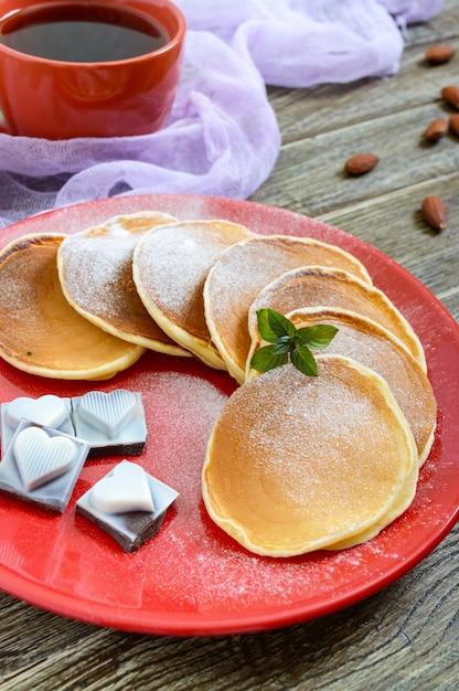 Leckere pfannkuchen mit puderzucker auf einem roten teller auf einem holztisch Premium Fotos