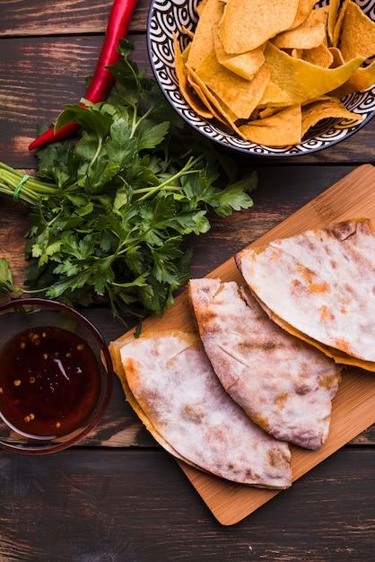 Leckere pita in der nähe von kräutern unter nachos mit sauce Kostenlose Fotos