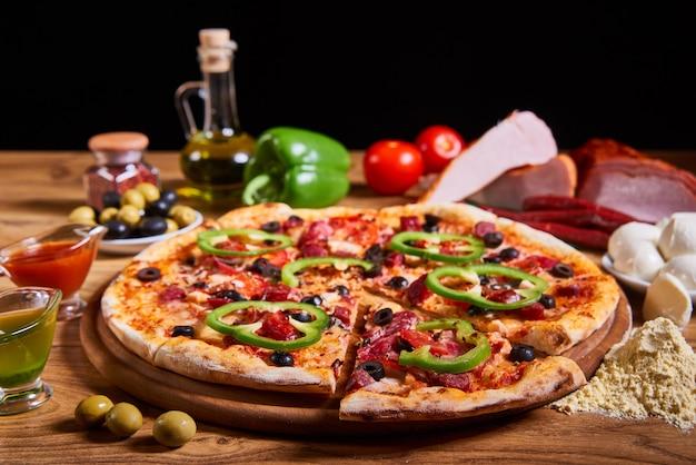 Leckere pizza der heißen großen pepperonis, zusammensetzung mit schmelzendem käsespeck-tomatenschinkenpaprika Premium Fotos