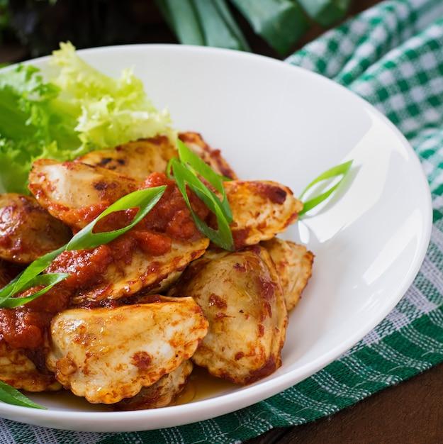 Leckere ravioli mit tomatensauce und frühlingszwiebeln Kostenlose Fotos