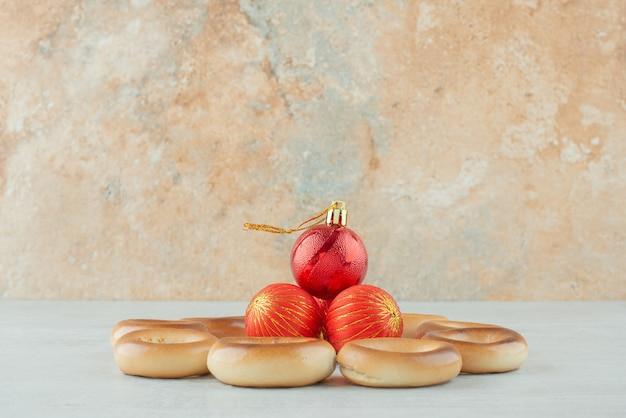Leckere runde süße kekse mit roten weihnachtskugeln auf weißem hintergrund. hochwertiges foto Kostenlose Fotos