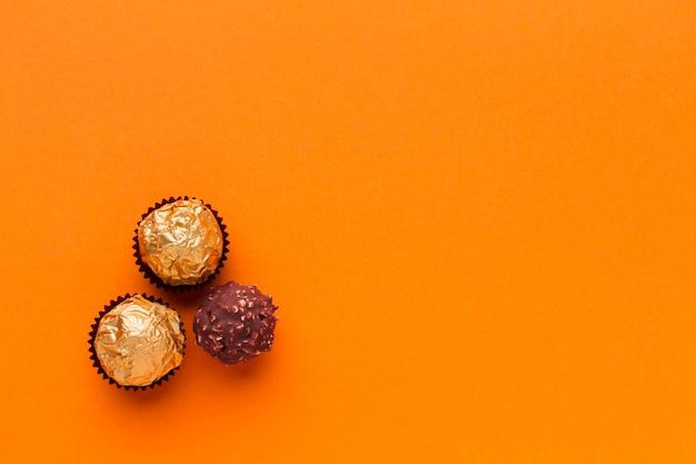 Leckere schokoladenpraline auf orange tabelle Kostenlose Fotos